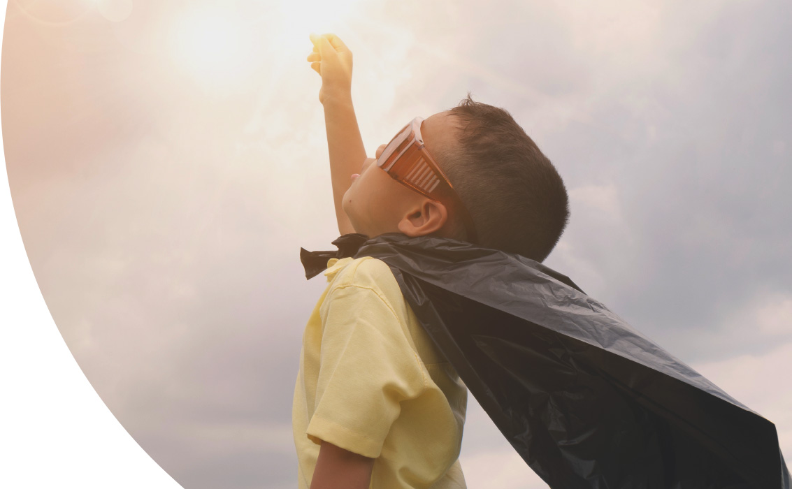 Boy with glasses wearing a black plastic cape with arm raised upward