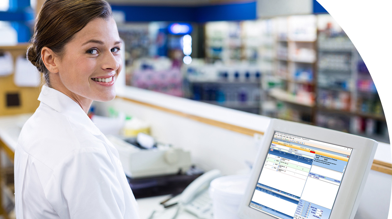 Pharmacist smiling in front of computer with IPS on screen